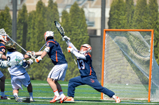 Evan Molloy reaches his stick high, attempting to make a save. He had seven on the day.